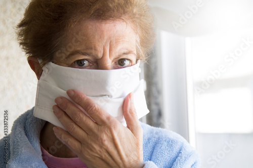 Foto Portrait of senior woman putting on medical mask in nursing home