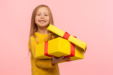 Child Satisfied With Good Present. Portrait Of Charming Funny Little Girl Opening Gift Box And Smiling To Camera, Celebrating Birthday, Christmas Holiday. Studio Shot Isolated On Pink Background