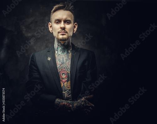 Photo Extravagant tattoo artist posing in a dark studio wearing a black tuxedo on a half-naked body, tattooed in a japanese irezumi style, looking self-assured and confident