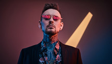Bold And Rebellious Male Model Posing In A Neon Studio Wearing A Black Tuxedo On A Half-naked Body, Fire-shaped Sunglasses And Tattooed In A Japanese Irezumi Style, Looking Self-assured. Vertical