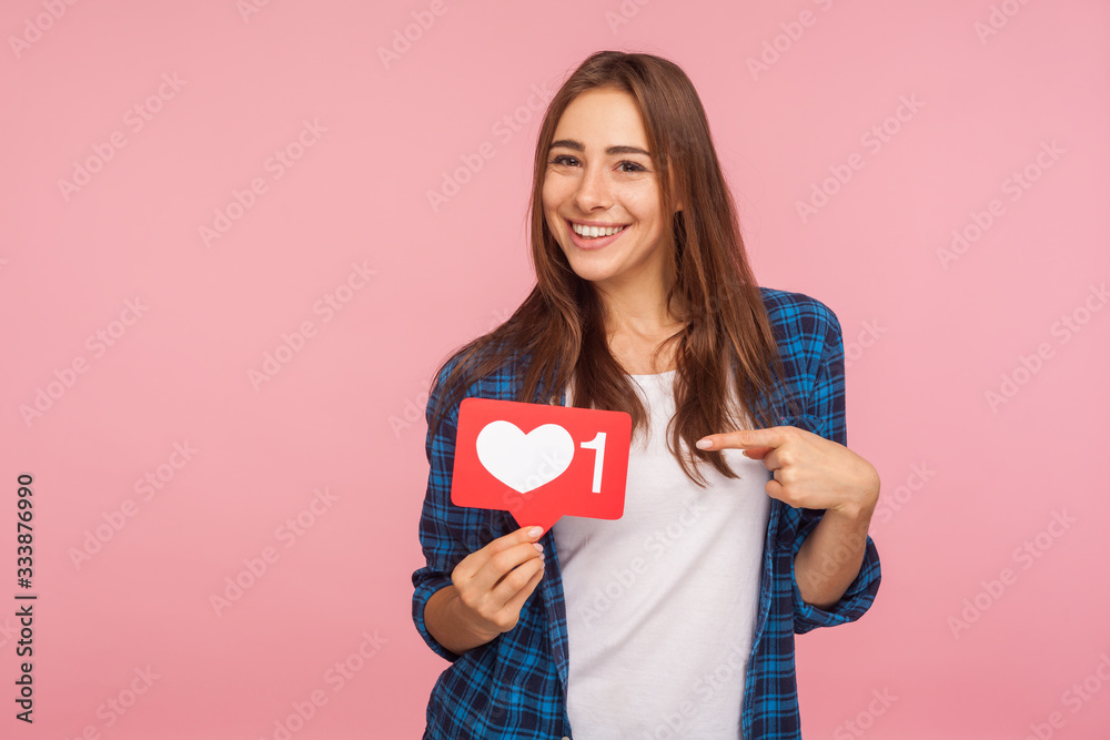 Fototapeta I like this content! Charming positive girl in checkered shirt smiling playfully and holding heart icon, social media button to enjoy trendy interesting blog. studio shot isolated on pink background