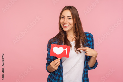 Fotomural I like this content! Charming positive girl in checkered shirt smiling playfully and holding heart icon, social media button to enjoy trendy interesting blog
