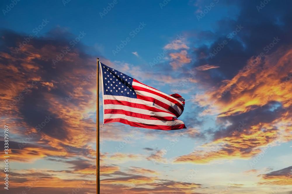 Fototapeta An American flag against a blue sky on an old rusty flagpole