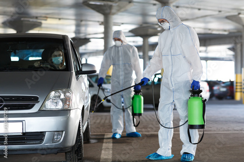 Fotomural Men in a protective suit and mask disinfecting car with spray