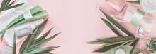 Modern Skin Care Beauty And Cosmetics Concept With Products Bottles With Mock Up, Aloe Vera And Palm Leaves On Pastel Pink Background. Natural Cosmetic. Banner. Top View. Eco Friendly. Zero Waste.