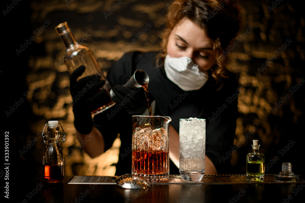 Fototapeta Lady bartender pours alcoholic drink into large glass with ice.