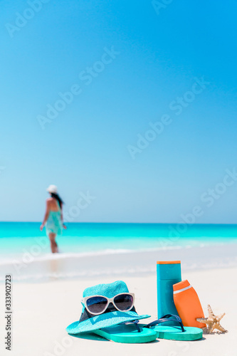 Fototapeta Suncream bottles, goggles, starfish and sunglasses on white sand beach backgroun