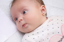 Portrait Of A Newborn Girl With An Earring In Her Ear