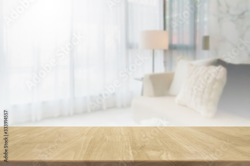 Fototapeta Empty wood table top and blurred living room in home interior with curtain window background. - can used for display or montage your products. obraz