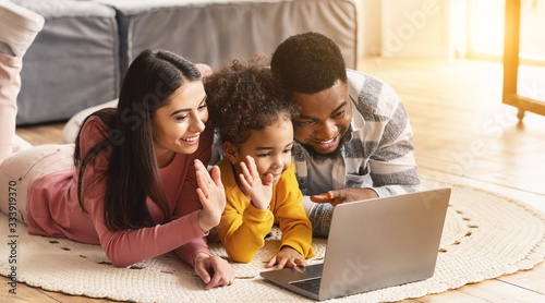 Mom and daughter waving their hands in laptop, dad smiling