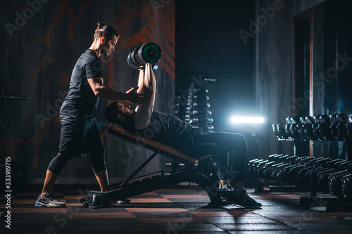young man has workout with personal trainer in modern gym Fototapeta