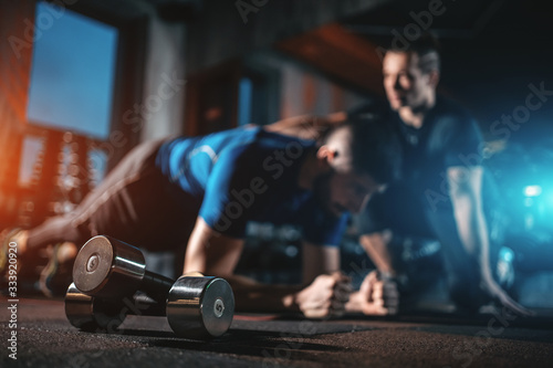 Fotografia young man has workout with personal trainer in modern gym