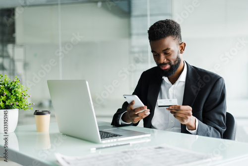 Fotografia African American man paying with credit card online while making orders via mobile Internet making transaction using mobile bank application