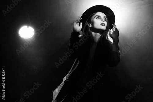 Photo Beautiful braless actress girl, wearing an unbuttoned blazer and a hat, poses and dances in the warm light rays of scenic illuminators in the theatrical fog