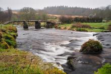 Fast Flowing Water Under The 13th Century Stone Clapper Bridge Originally Built To Enable Pack Horses To Cross The East Dart River At Postbridge, Dartmoor National Park, Devon, UK