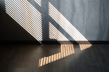 Light And Shadow From The Window. Thin Lines Of Light On The Wall And Floor. The Texture Of The Plaster. Shadow From The Blinds. Place For Your Text.