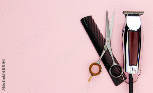 Tools for cutting and styling hair on a pink background. Professional hairdressing tools and accessories.