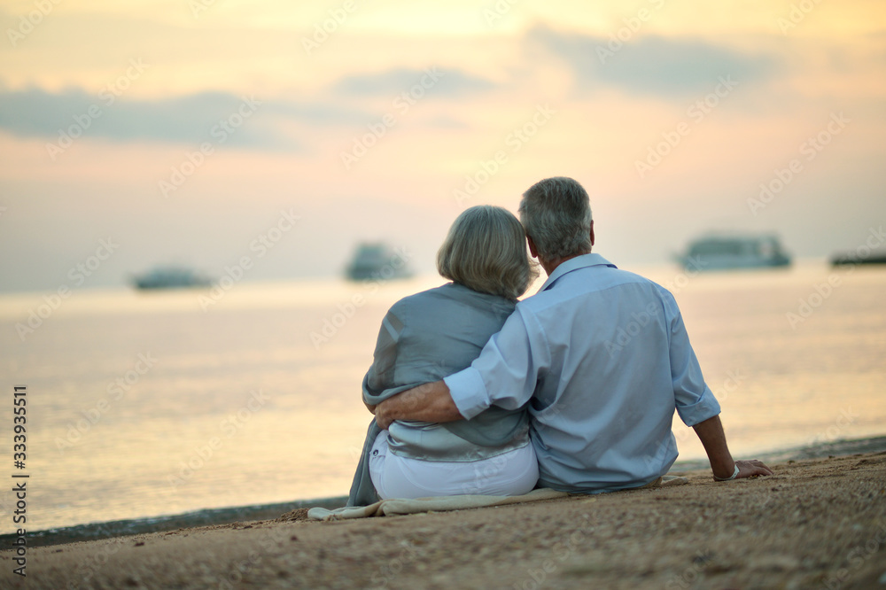 Fototapeta Portrait of mature couple relaxing on beach
