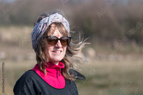 Fotografie, Tablou An attractive lady wearing sunglasses has her eyes closed due to bright sunshine