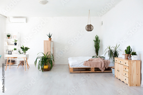 Cozy bedroom area at luxury studio apartment with a free layout in a loft style with big panoramic window and green plant Canvas Print