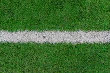 White Stripe On The Green Soccer Field Top View. White Line On Artificial Football Field