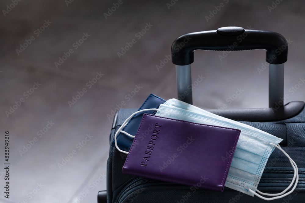 Fototapeta Travel suitcase, passport and medical mask. The ban on travel during the epidemic of the coronavirus and the introduction of quarantine concept.