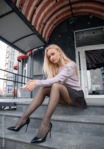 Fototapeta Girl with perfect legs in pantyhose at the city square.