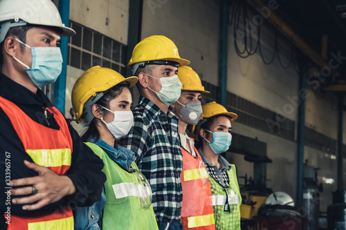 Obraz Factory workers with face mask protect from outbreak of Corona Virus Disease 2019 or COVID-19. - fototapety do salonu