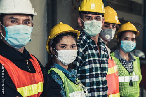 Fototapeta Factory workers with face mask protect from outbreak of Corona Virus Disease 2019 or COVID-19
