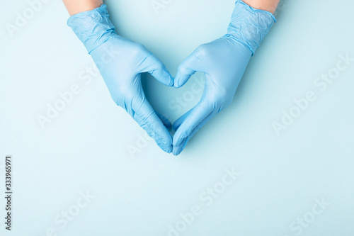 Photo Doctor's hands in medical gloves in shape of heart on blue background with copy space
