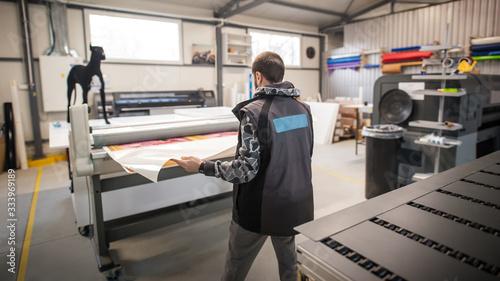 Fotografía Technician works in large printing press hall and printshop office
