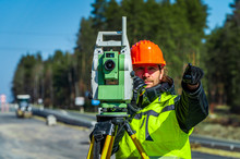 Surveyor Engineer With Equipment (theodolite Or Total Positioning Station) On The Construction Site Of The Road Or Building With Construction Machinery Background