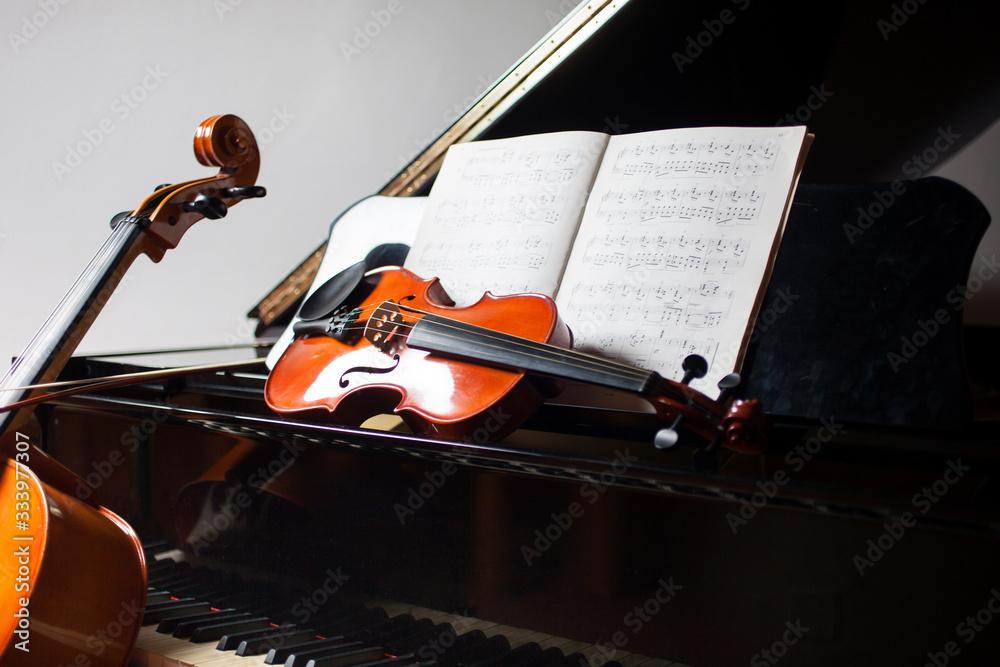 Fototapeta Classical music concept: cello, violin, piano and a score