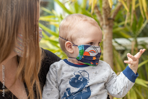 Slika na platnu Portrait of baby and mother together with homemade reusable protective face mask against coronavirus on face