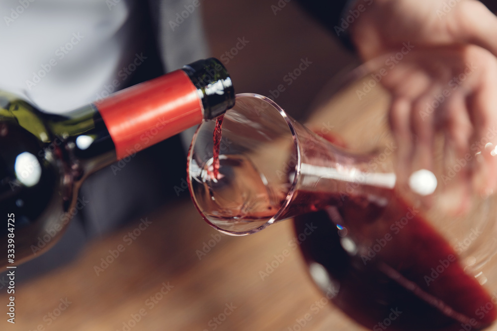 Fototapeta Sommelier man pours red wine into decanter for aeration of taste and aroma