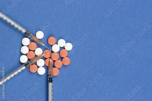 Photo A syringe with an injection solution and vitamins with pills