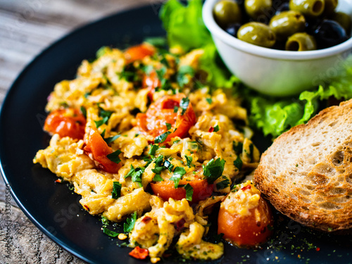 Fototapeta Breakfast - scrambled eggs with vegetables and toasted bread on wooden backgroun