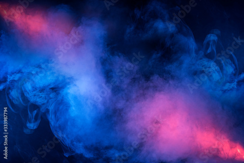 Abstract texture of backlit smoke in red blue on a black background.