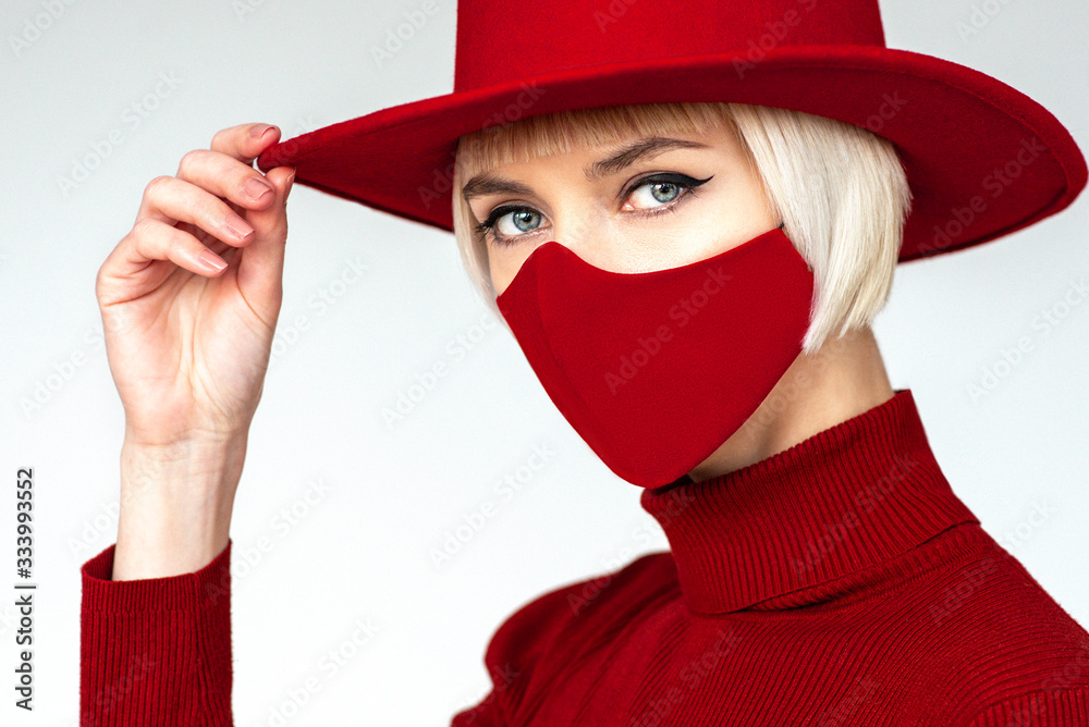 Fototapeta Woman wearing trendy fashion outfit during quarantine  of coronavirus outbreak. Total red look including protective stylish handmade face mask