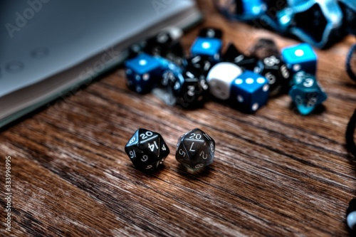 Fotografia Multiple gaming dice on wooden table with 20 shown on a pair of d20