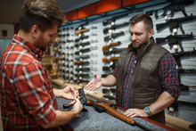 Man With Owner Choosing Handgun In Gun Shop
