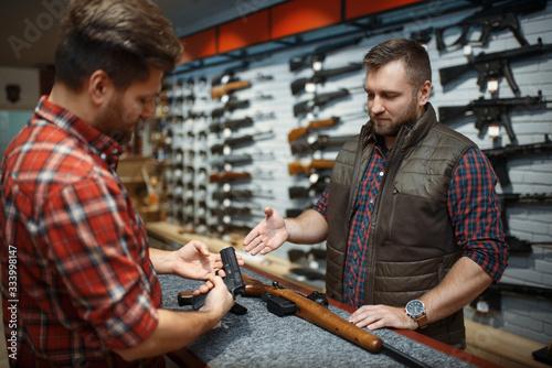 Man with owner choosing handgun in gun shop Wallpaper Mural