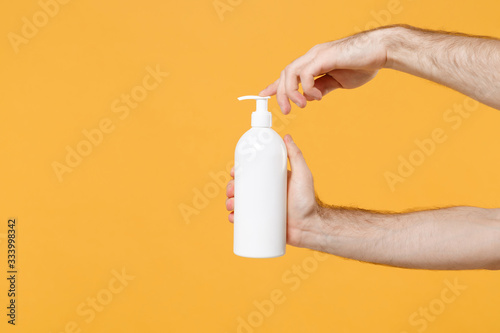 Obraz Close up cropped photo of male hold in hand bottle with antibacterial sanitizer soap isolated on yellow background. Epidemic pandemic coronavirus 2019-ncov sars covid-19 flu virus. Mock up copy space. - fototapety do salonu