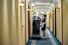 Quality Cleaning. Full-length Shot Of Hotel Maid In Uniform Standing In Front Of Chambermaid Trolley. Room Service Concept.