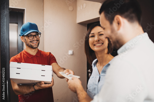 Fototapeta Smiling young couple receiving pizza from delivery man at home. obraz