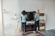 Quality cleaning. Two professional cleaners in uniform giving wiping TV screen while working together in the living room