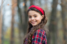 Smiling Girl Wear Knotted Headband. Biggest Hair Accessory Trends. Adorable Little Girl Checkered Shirt Wear Red Headband. Fashion Trend. Accessories. Fancy Child Nature Background. Padded Headband