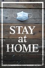 STAY At HOME と書かれた板とマスク