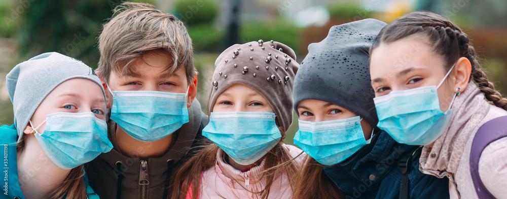 Fototapeta School-age children in medical masks. portrait of school children.