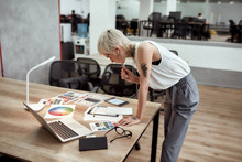 New Project. Young Stylish Blonde Tattooed Female Designer Making Some Sketches And Working With Color Swatch Samples While Standing Near Office Desk
